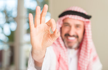 Middle age arabian man at home doing ok sign with fingers, excellent symbol