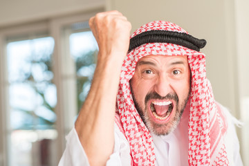 Middle age arabian man at home annoyed and frustrated shouting with anger, crazy and yelling with raised hand, anger concept