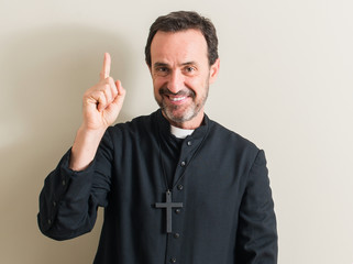Senior priest religion man surprised with an idea or question pointing finger with happy face, number one