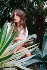 An attractive young woman wearing shorts and T-shirt among Agave plants and date palms