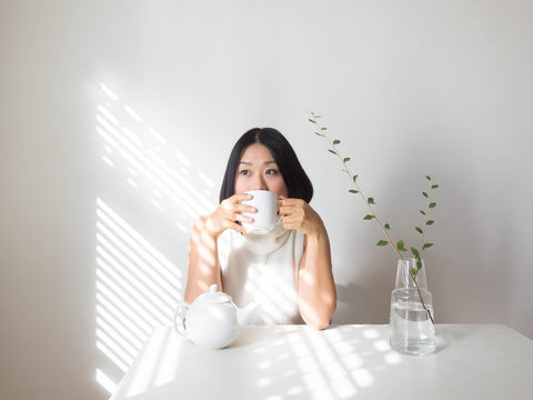 Portrait of young woman sipping tea at table with natural light