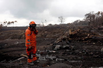 A member of the Guatemala's disaster management agency (CONRED) gestures while inspecting an area affected by a lahar from Fuego volcano at El Rodeo