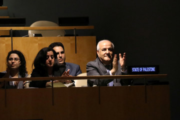 Palestinian Ambassador to the United Nations Riyad Mansour applauds following the adoption of a draft resolution by the United Nations General Assembly to deplore the use of excessive force by Israeli troops against Palestinian civilians in New York