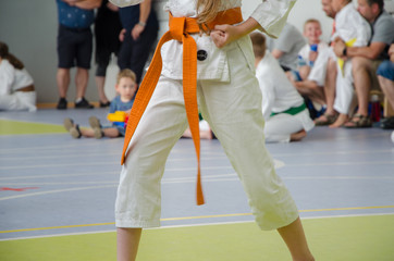 karate competition. a girl in kimono with orange belt. no face. the hand is compressed in a fist