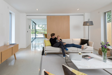 Couple relaxing in their modern sitting room. Views through to other areas of the house.