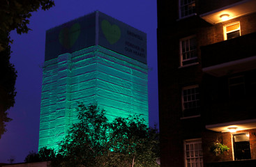 Grenfell Tower is seen covered and illuminated with green light one year after the tower fire in Britain, in London