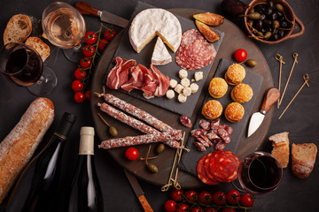 Appetizers table with differents antipasti, cheese, charcuterie, snacks and wine. Mini burgers, sausage, ham, tapas, olives, cheese and baguette over grey concrete background. Top view, flat lay