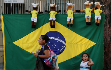 A Brazilian flag and dolls for sale are seen as a woman and a child walk ahead of the 2018 World Cup, in Rio de Janeiro