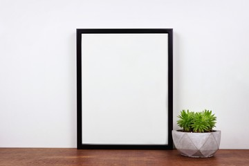 Mock up black frame with succulent plant on a shelf or desk. Wood shelf and white wall. Portrait frame orientation.