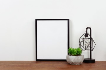 Mock up black frame, succulent plant and industrial style lamp on a shelf or desk. Wood shelf and white wall. Portrait frame orientation.