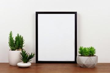 Mock up black frame with succulent plants on a shelf or desk. Wood shelf and white wall. Portrait frame orientation.