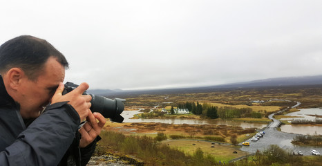 Profile of a man traveler with a camera taking pictures of nature