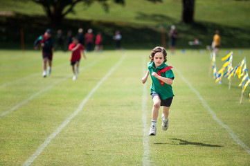 Child with a determined expression winning a running race