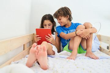 Kids watching cartoons on tablet in bed.