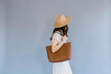 Fashionable woman holding bag against backdrop