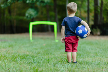 Young boy looking towards a practice goal with a soccer ball under his arm