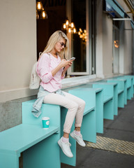 Beautiful woman with coffee and smartphone