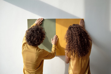 Women hanging painting on wall