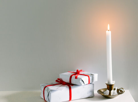 Christmas gifts on a mantlepiece with a lit candle. With copy space.