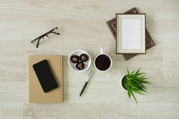 Notebooks with hot coffee and cookies on wood background. Rustic home office.