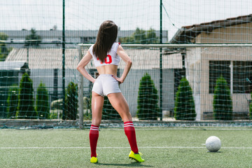 Young female football player on football field kicking ball