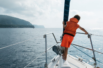 Little sailor in life vest standing on bow of yacht.