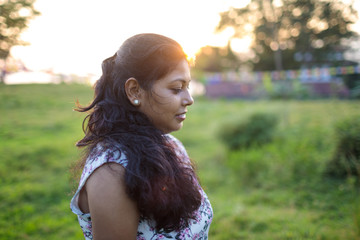 Portrait of young woman in the field at sunset