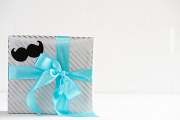 Happy fathers day concept. beautiful gift box with black mustache paper on white pastel wooden table background.