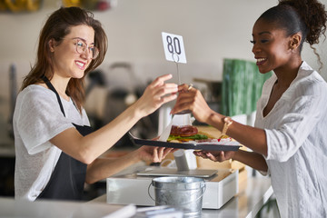 waitress handing order of food on tray to customer