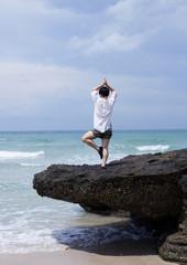 Yoga meditation of Asian women, in the beautiful seaside natural rock