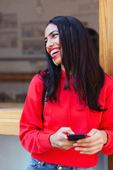 Portrait of a smiling latin woman wearing red sweater in the city.