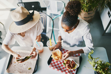 two friends eating healthy vegan food at restaurant together