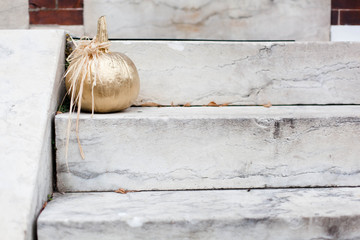 Gold decorative pumpkin on marble steps