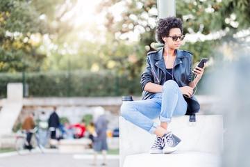 Young woman holding a cell phone outdoors