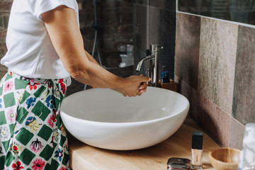 Woman washing her hand in her bathroom