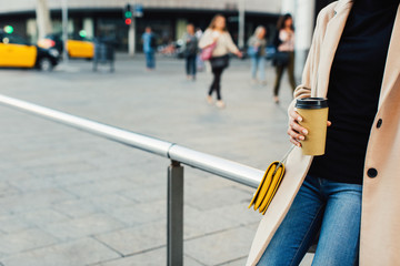 Stylish woman in the city drinking a take away coffee.