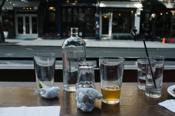 empty glasses sit on table looking out a city street