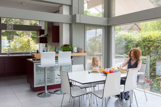 Mother and daughter having lunch inside a modern dining area of a house.