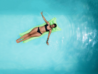 Woman on green inflatable in the swimming pool