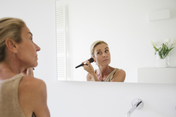 Beautiful mature woman putting face powder to her face