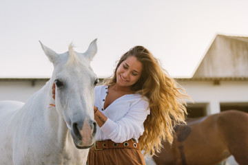 Happy young woman caressing a white horse