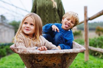 Mom and her kids having fun in wheelbarrow.