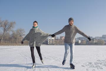 Beautiful couple ice skating on the lake