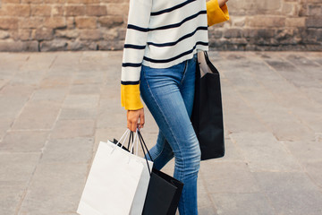 Anonymous woman walking with shopping bags on the street.