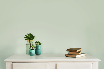 hall table with plant, books and blank wall