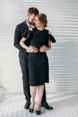 Front view stylish portrait of young husband and wife wearing black outfits and posing indoors