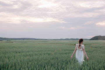 Back view of young woman walking by the field of whet in white linen dress