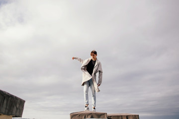 Portrait of young brunet man balancing on the roof