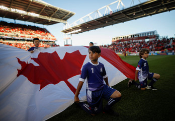Kids hold a Canadian flag at an MLS soccer match, at BMO Field, a venue for the 2026 FIFA World Cup, in Toronto