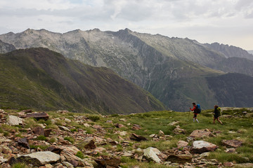 Scenic landscape with a couple of hikers walking the green and rocky mountains